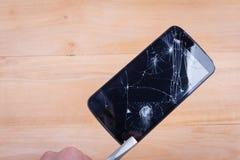 Un téléphone portable avec un écran cassé est maintenu par les pinces que l'homme européen tient Image libre de droits