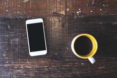 Un téléphone portable blanc avec l'écran de bureau noir vide avec la tasse de café sur la table en bois de vintage Photographie stock libre de droits