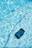 Un téléphone portable s'étendant sur les étapes d'une eau du fond de piscine photographie stock libre de droits