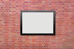Un tabellone per le affissioni in bianco allegato ad un muro di mattoni di esterno delle costruzioni Fotografia Stock
