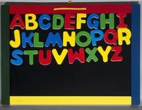 Un tableau noir avec les lettres de l'alphabet Photographie stock libre de droits