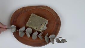 Un tablero de madera redondo con una barra del jabón del eucalipto de la lavanda y de una ramita delante de ella