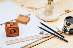 Un taccuino aperto e un righello con due matite e un puzzle su un fondo di legno immagini stock libere da diritti