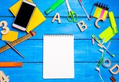 Un taccuino bianco sullo scrittorio del ` s dello studente fra i rifornimenti di scuola Spazio per testo, spazio della copia Il c immagini stock libere da diritti