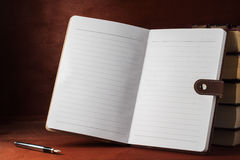 Un taccuino con i manuali su una tavola di legno Immagine Stock Libera da Diritti