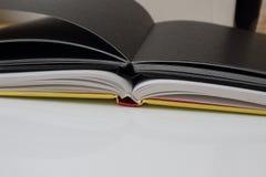 Un taccuino nero che si trova sul Libro Bianco immagini stock libere da diritti