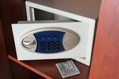Un taco de d?lares y una caja fuerte abierta en el armario Mantener el dinero un lugar seguro de ladrones El concepto de protecci fotografía de archivo libre de regalías