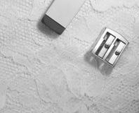 Un taille-crayons et une gomme se trouve sur la surface blanche de dentelle photographie stock