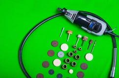 Un taladro gris con los accesorios de la perforación en la opinión aérea del fondo verde Imagen de archivo libre de regalías