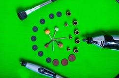 Un taladro gris con los accesorios de la perforación en la opinión aérea del fondo verde Imagen de archivo