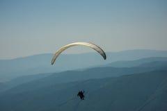 Un tandem di parapendio sorvola una valle della montagna su una somma soleggiata fotografia stock