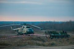 Un tanque ocultado detrás de árboles y del helicóptero de pino en polígono foto de archivo