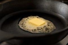 Un tapotement de beurre fondant sur une poêle noire de fonte photo libre de droits