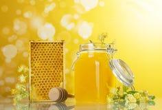 Un tarro abierto de la miel, de panales y de la cuchara de madera en fondo amarillo Imagen de archivo libre de regalías