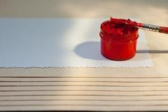 Un tarro con la pintura roja y un cepillo en una hoja del Libro Blanco Imagen de archivo