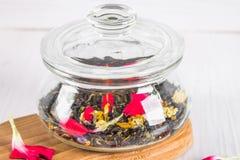 Un tarro con un té floral herbario negro en una tabla de madera blanca Fotografía de archivo libre de regalías