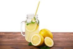 Un tarro de albañil de agua con el jugo de limón fresco y la menta verde clara en la tabla de madera del marrón oscuro, aislado e Foto de archivo libre de regalías