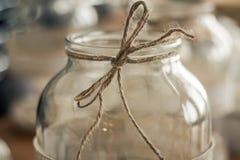 Un tarro de cristal con un arco marrón se sienta en una tabla de cocina foto de archivo libre de regalías