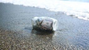 Un tarro de cristal con los dólares de los billetes contra un mar agita el fondo Acumule los ahorros en licencia por el mar o almacen de metraje de vídeo