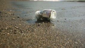 Un tarro de cristal con los dólares de los billetes contra un mar agita el fondo Acumule los ahorros en licencia por el mar o almacen de video