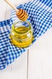 Un tarro de la miel con una cuchara, en una tabla blanca con una toalla azul La miel se vierte de una cuchara Fotos de archivo