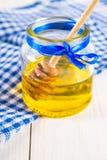 Un tarro de la miel con una cuchara, en una tabla blanca con una toalla azul Foto de archivo