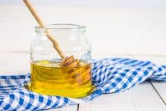 Un tarro de la miel con una cuchara, en una tabla blanca con una toalla azul Imagen de archivo libre de regalías