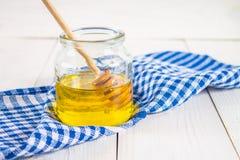 Un tarro de la miel con una cuchara, en una tabla blanca con una toalla azul Imagen de archivo