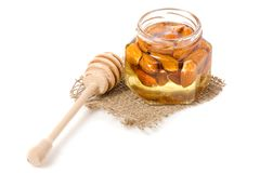 Un tarro de la miel con una cuchara para las almendras de las nueces de la miel Foto de archivo libre de regalías