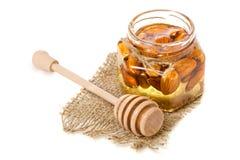 Un tarro de la miel con una cuchara para las almendras de las nueces de la miel Imagen de archivo
