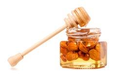 Un tarro de la miel con una cuchara para las almendras de las nueces de la miel Imagen de archivo libre de regalías