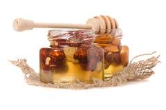 Un tarro de la miel con una cuchara para las nueces de la miel Foto de archivo libre de regalías