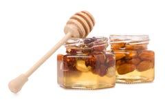 Un tarro de la miel con una cuchara para las nueces de la miel Fotos de archivo