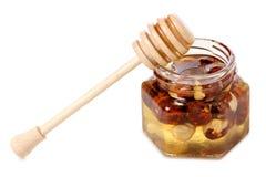 Un tarro de la miel con una cuchara para las nueces de la miel Fotos de archivo libres de regalías