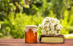 Un tarro de la miel de la flor, de un libro viejo y de un ramo de wildflowers Copie el espacio Fotografía de archivo