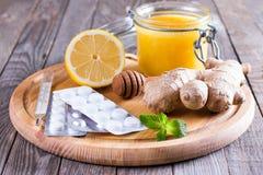 Un tarro de la miel, limón, jengibre, miel en un fondo de madera Tabletas y termómetro Luchar el frío común Imagen de archivo libre de regalías