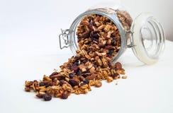 Un tarro de muesli dispersado en una tabla blanca, muesli, cereales para sano foto de archivo