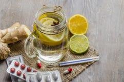 Un tarro del maison con té del jengibre y del limón con las píldoras y termómetro en el fondo de madera Fotos de archivo libres de regalías