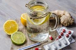 Un tarro del maison con té del jengibre y del limón con las píldoras y termómetro en el fondo de madera Imagenes de archivo