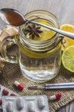 Un tarro del maison con té del jengibre y del limón con las píldoras y termómetro en el fondo de madera Imagen de archivo libre de regalías