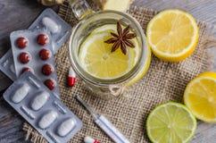 Un tarro del maison con té del jengibre y del limón con las píldoras y termómetro en el fondo de madera Fotografía de archivo