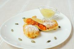 Un tarte de potiron avec la poudre de sucre et sauce douce dans un plat blanc, un arrangement léger confortable de table, une ali photos stock