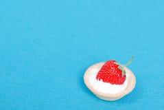 Un tartlet con la crema y la fresa en un fondo azul, top Imagen de archivo libre de regalías