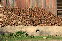 Un tas en bois est stocké devant un entrepôt dans un village (Bhutan) Photos libres de droits