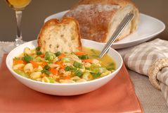 Un tazón de fuente de sopa de tallarines del pollo con pan rústico y un vidrio de w Fotos de archivo libres de regalías