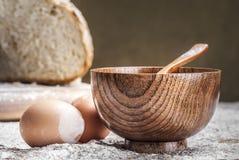 Un tazón de fuente de madera y dos huevos Fotos de archivo libres de regalías