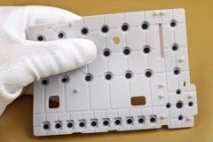 Un technicien commande la qualité d'un clavier en caoutchouc de commutateur pour le dvice mobile photographie stock