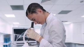 Un tecnico di laboratorio femminile che si siede ad una tavola accanto ad un computer portatile in un laboratorio chimico esamina archivi video