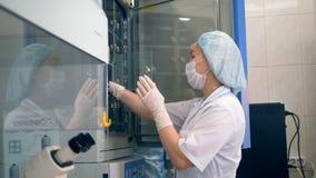 Un tecnico di laboratorio preleva un campione da un frigorifero video d archivio