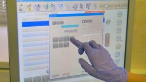 Un tecnico sceglie le regolazioni dell'analisi del sangue su un touch screen video d archivio